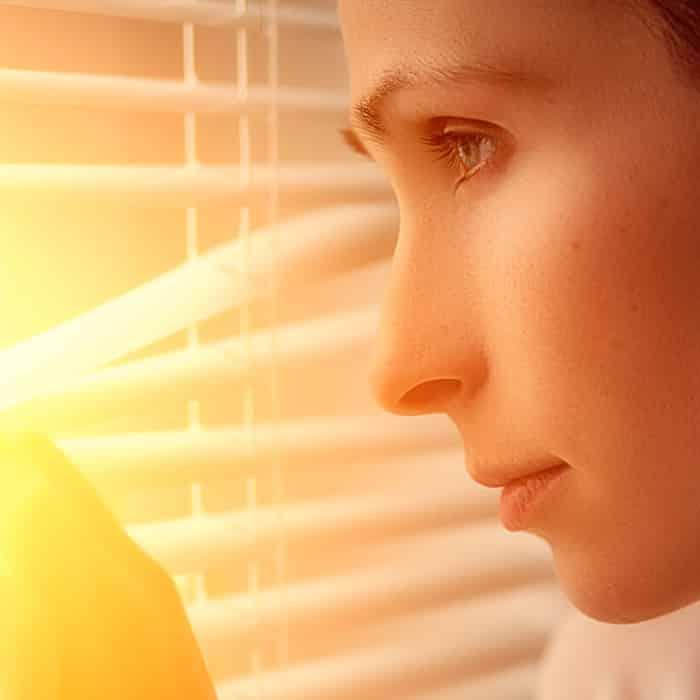 Refenrenz Herkenhoff Frau schaut durch Rollos aus dem Fenster