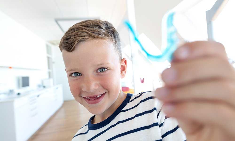 Ein Junge ohne Schneidezähne lächelt und hält dabei eine lose Zahnspange in der Hand
