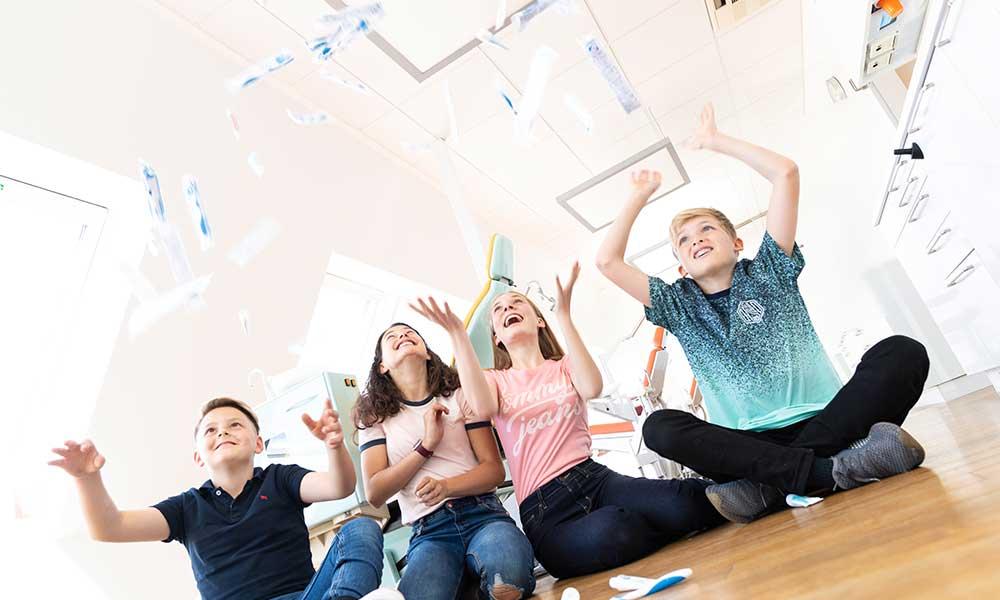 Vier Kinder werfen lachend Zahnpastatuben in die Luft