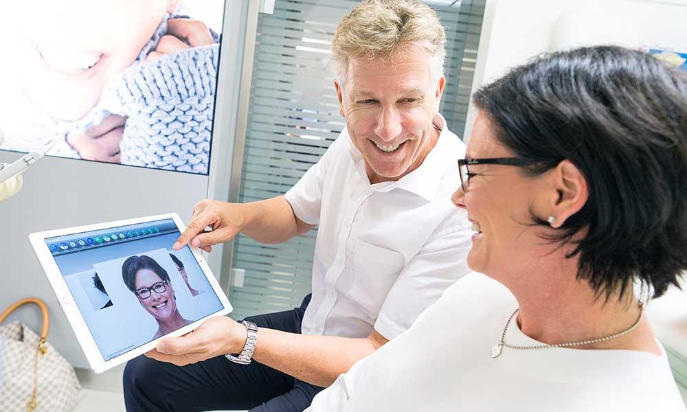 Arzt zeigt seiner Patientin auf einem Tablet Fotos von ihr