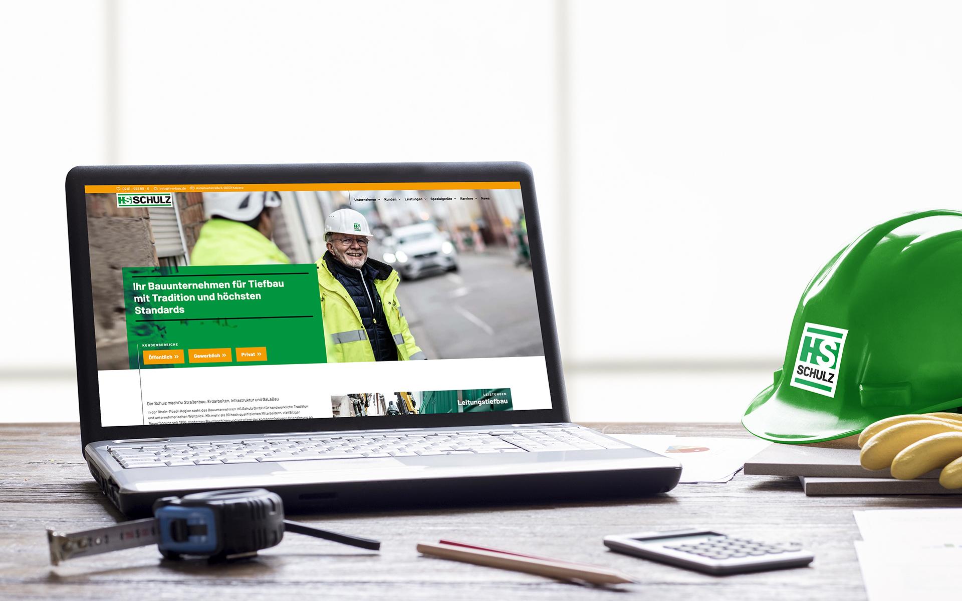Laptopbildschirm zeigt Webdesign von HS Schulz. Um den Laptop liegen verschiedene Gegenstände aus dem Baubereich wie Maßband, Schutzhelm, Handschuh, Stift und Taschenrechner.