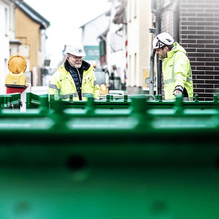 Zwei Männer mit gelben Warnjacken und Schutzhelmen stehen vor einem grünen Baustellenzaun