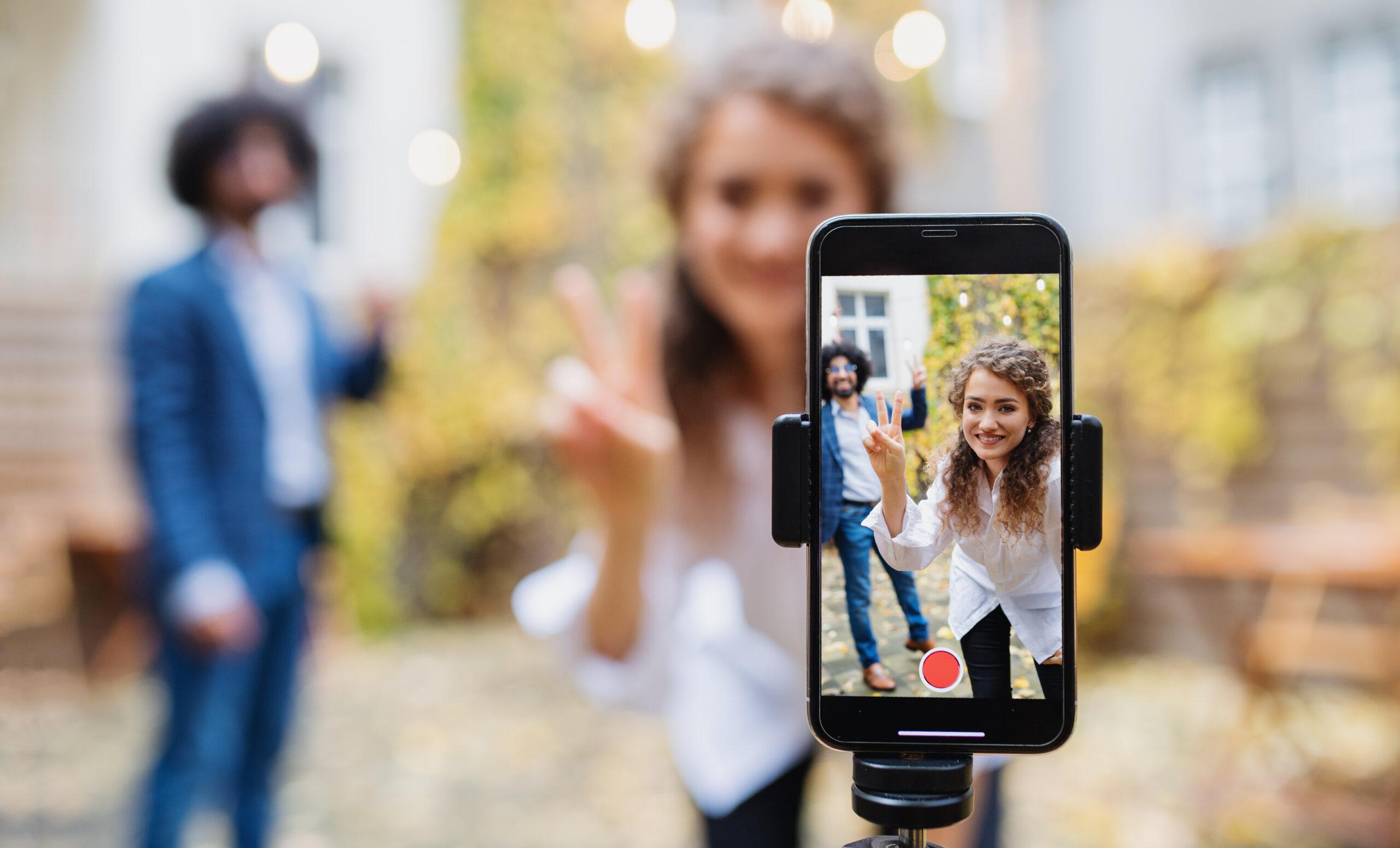 Zwei junge Menschen nehmen ein TikTok-Video auf: TikTok als Kommunikationsmedium für Unternehmen